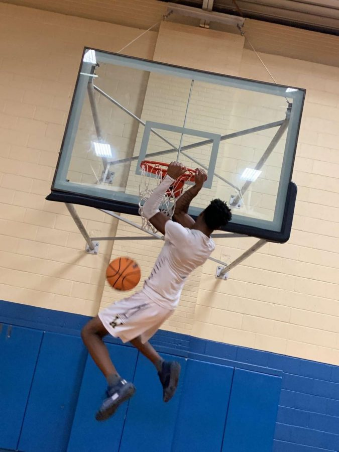 Devin Holmes, power forward gets a lucky dunk during practice.